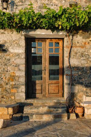 Wodden door with vines in Elounda village Stok Fotoğraf