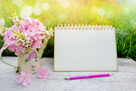 pink flower on wooden table in soft pastel tone of bokeh nature green grass , including blank page paper of calendar ,pencil,spring morning sunlight background Фото со стока