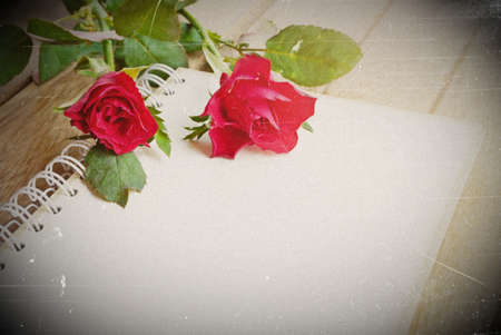 letter writing: red roses flower and open notebook for text on wooden background, soft vintage tone
