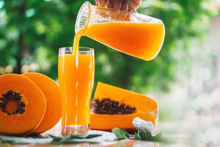 Donna versando a mano il succo di papaia su bicchieri con fetta di papaia su sfondo di legno, frutta sana e dietetica