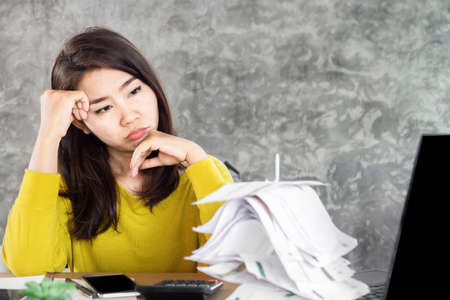 stress Asian woman looking at unpaid financial bills and having problem with debt sitting at desk with worried face