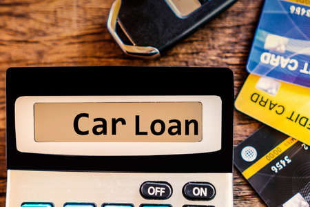 car loan concept with text,calculator and credit card and car key ,calculating for debt payment background