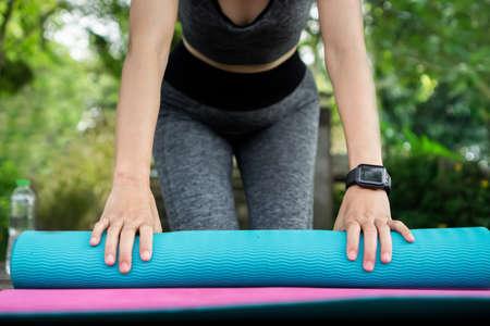 closeup woman arm wearing smart watch folding yoga mat outdoor in green park