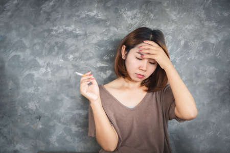 depressed Asian woman smoking cigarette with unhappy face sitting alone next to the wall