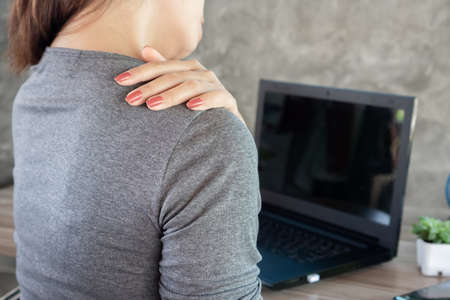 woman suffering from office syndrome neck and shoulder pain sitting on chair with laptop on desk
