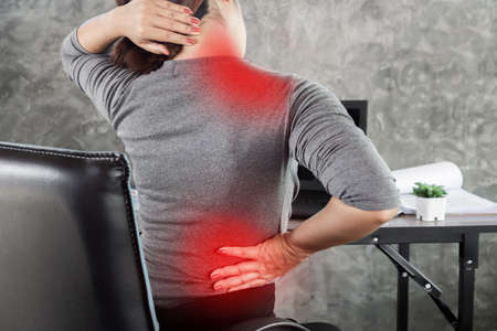 woman suffering from office syndrome having lower back pain, neck and shoulder pain sitting on chair Stock fotó