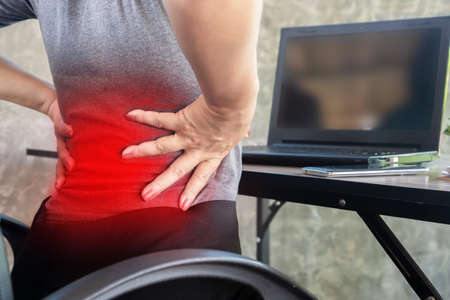woman suffering from office syndrome having lower back pain sitting on chair