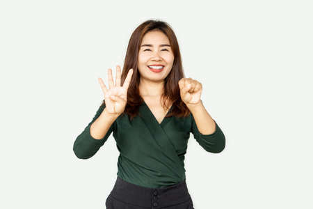 Happy Asian woman showing finger age 40 years old and smiling with confident to camera standing over gray background