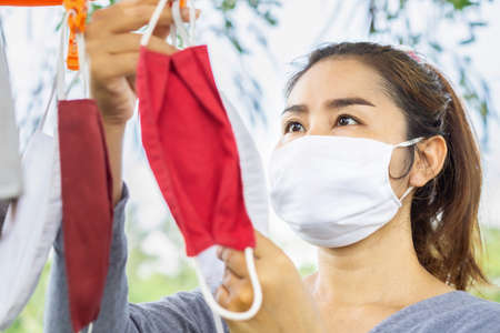 Asian woman hand washing fabric face mask and hanging to dry outdoor, new normal during covid-19 pandemic concept