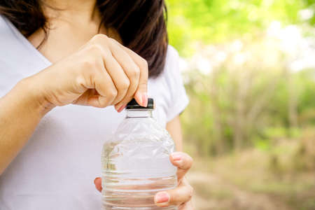 woman hand holding bottle of fresh water drinking outdoors in a park