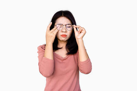Asian woman hand holding eyeglasses the other hand rubbing her eye pain, blur vision standing isolated on white background Imagens