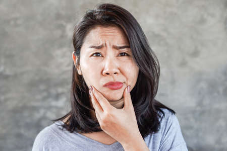 depressed Asian woman having problem with Bell's Palsy/Facial Palsy, hand holding her face Foto de archivo