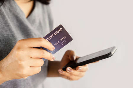 closeup woman hand using smart phone and credit card paying from home Stok Fotoğraf