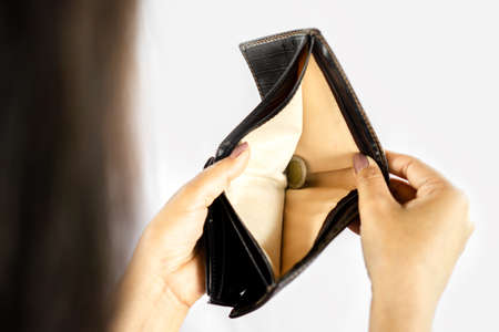 poor woman hand open empty purse another hand holding only one coin ,payday and bankrupt concept