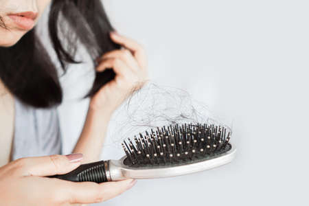 Asian woman brush her hair having problem with hair loss fall on comb