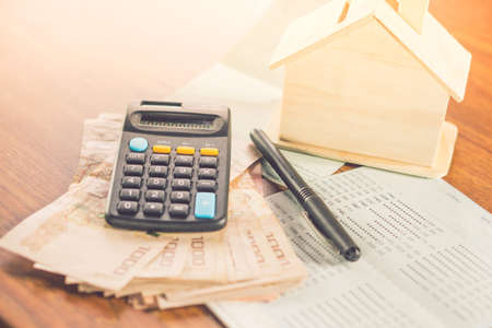 paper currency, calculator, saving account and house model on desk, concept of buy ,rent, pay tax for home