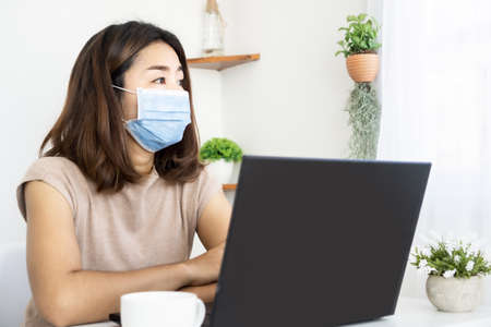depressed Asian woman worker wearing face mask feeling bored to work from home tired with self quarantine