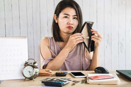 poor Asian woman looking for money in empty wallet having problem with debt