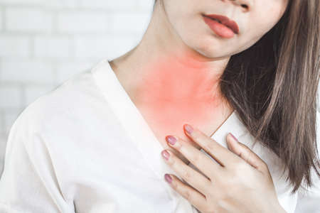 Asian woman suffering from acid reflux or heartburn