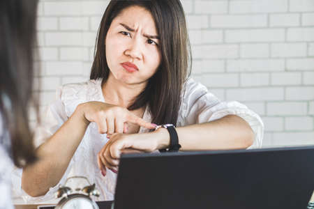 Angry Asian female manager pointing at her watch complaining her employee for coming late