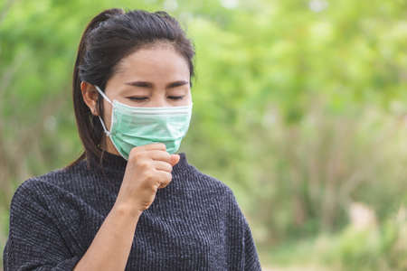 sick Asian woman wearing mask feeling unwell and coughing outdoors in a park