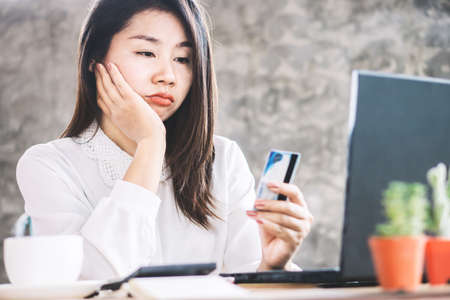 sad Asian woman having problem with limit credit card for online shopping, over spending concept Standard-Bild