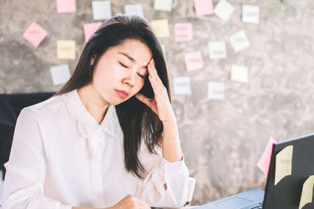 overworked Asian business woman tired with working sitting at office desk Фото со стока