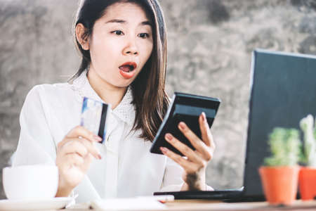 shocked Asian woman hand counting expenses on calculator having problem with credit card debt Фото со стока