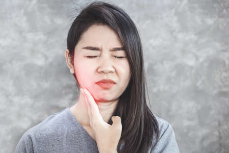 Asian woman suffering from toothache problem hand holding and painful Stockfoto