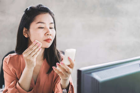 Asian business woman putting make up on face sitting at office desk