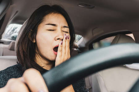 Tired sleepy Asian woman yawning during driving car