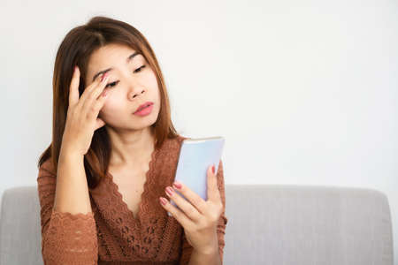 Asian woman having problem with eye pain tired from watching mobile phone screen Standard-Bild