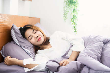 young Asian woman peacefully  sleeping well on comfortable soft bed Zdjęcie Seryjne