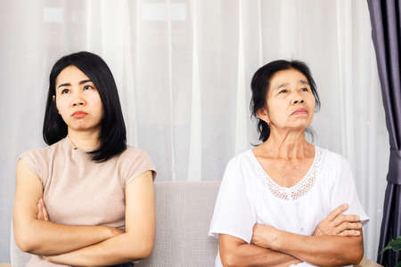 depressed Asian mother and daughter sitting at sofa angry, quarrel, ignoring each other , serious relationship in family concept Banque d'images