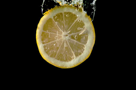 Sliced lemon in the water on black background photo