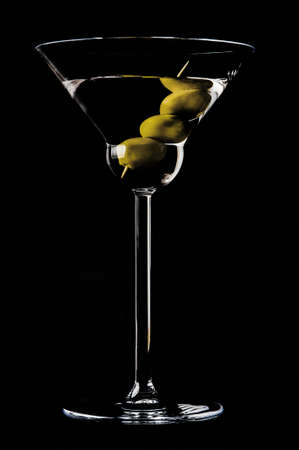 Martini with olives on a black background photo
