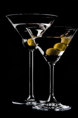 copa de martini: Martini con aceitunas en un fondo negro