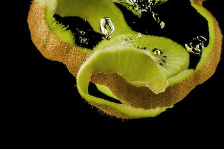 Kiwi fruit in water on a black background photo