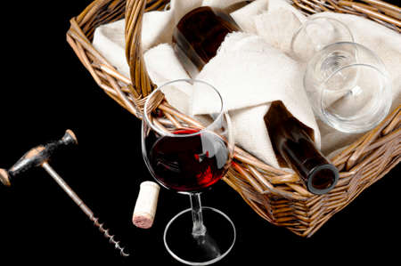 The glass of wine and picnic basket with bottle of wine on a black photo