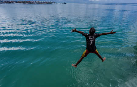 sky dive: boy jumping into the sea