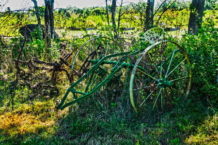 farm equipment: farm equipment covered by plants at an abandon  farm.