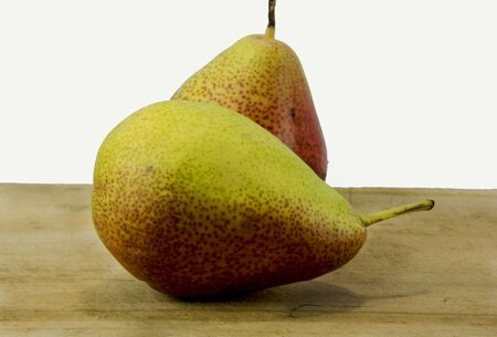 two pears on a chop board against a white back ground.