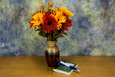 note pad with a pen and assorted flowers