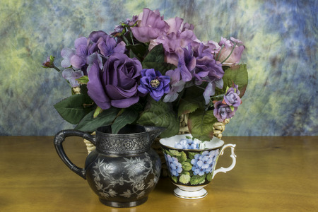 assorted flowers with  a cup and creamer.