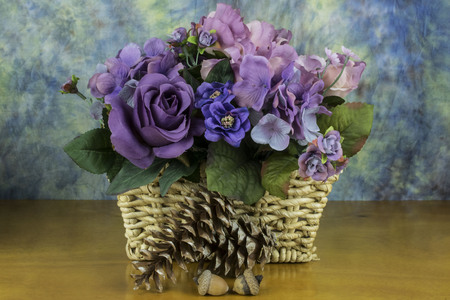 assorted flowers in a basket with pine cones and acorn.