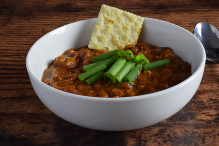chili with a cracker and green onions Stock Photo