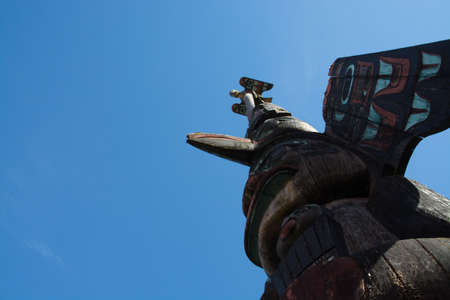northwest indian art: Totem pole reaching to the sky in Ketchikan Alaska.