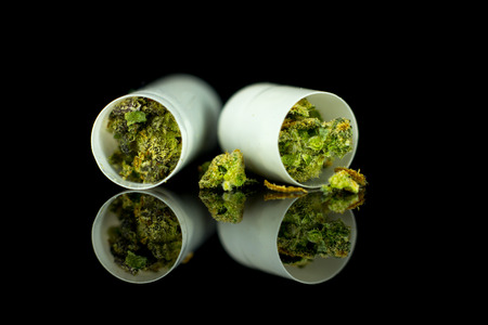 Medical Capsules of Cannabis - marijuana flower in tablets, cannabis on the mirror black background.