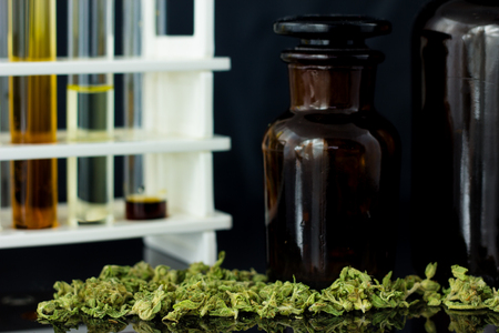 Medical Oil of Cannabis - oil test tubes with old antique apothecary jar with marijuana on the black mirror background.
