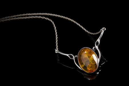 silver jewellery: an oval amber stone set in a silver pendant with attached silver link chain on shiny black background